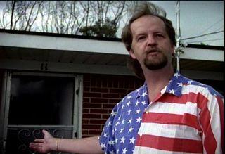 Mark Byers gestures towards his home